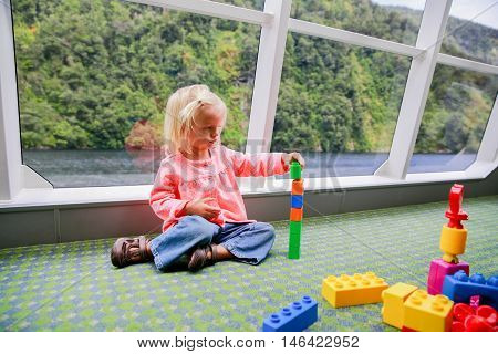 Adorable kid playing with constructor on a boat lake Te Anau New Zealand poster