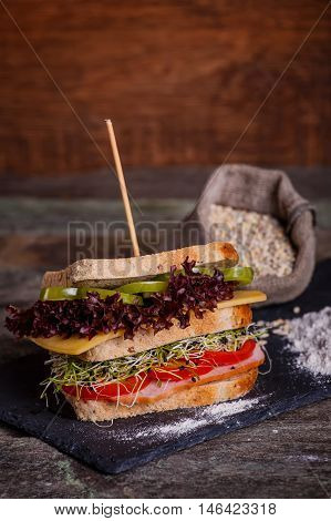 Sandwich With Cereals Bread With Lettuce, Slices Of Fresh Tomatoes And Sweet Peper, Ham, Prosciutto,