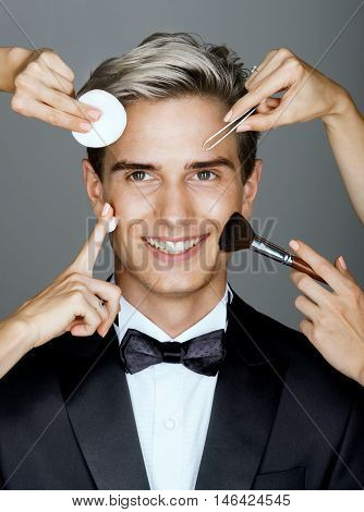 An abundance of style. Beautiful man surrounded by the multifunctional service (beautician and stylist). Photo of happy stylish man on gray background. Grooming himself