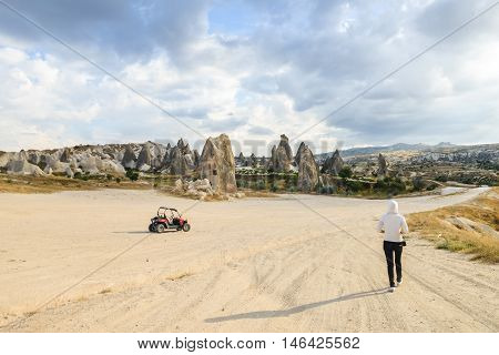single girl walking toward skyline, with one ATV vehicle parked around in wild valley in Cappadocia, Turkey, surrounded among the rocks, dunes and  hills in Goreme National Park, typical terrain landscape in Cappadocia poster