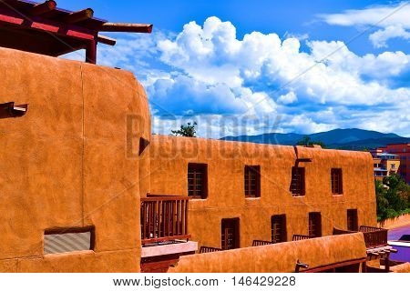 Building with modern adobe architecture and a beautiful sky with cumulus clouds taken in Santa Fe, NM