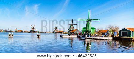 Zaanse schans, Netherlands - April 1, 2016: Windmills panorama in Zaanse Schans, North Holland, traditional village, tourists, blue sky