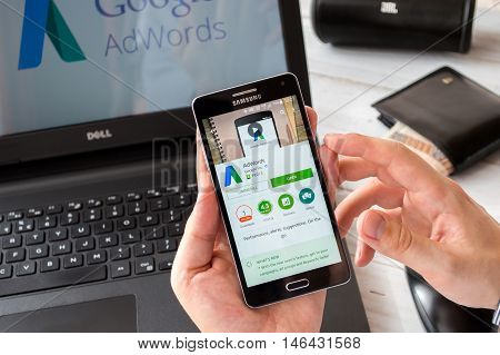WROCLAW POLAND- SEPTEMBER 09th 2016: Businessman prepares to install Google Adwords application on Samsung A5. Google Adwords is advertising system that allows to display sponsored links in Google search results.