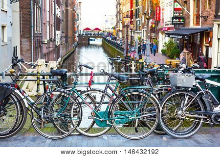 Amsterdam, Netherlands - April 1, 2016: Traditional old buildings, people, canal and bridge view with bicycles in Amsterdam, the Netherlands