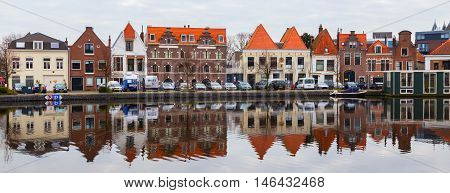 Haarlem, Netherlands - April 2, 2016: Picturesque landscape panorama with beautiful traditional houses reflection in canal,  Haarlem, Holland