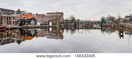 Panorama landscape with beautiful traditional houses reflection in canal, Haarlem, Holland