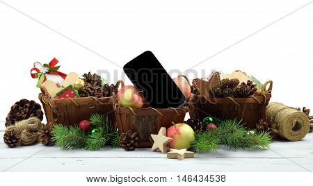 Christmas decoration in a rustic style and desired gift for Christmas - a smartphone.Branches of trees and wooden baskets with gifts and handmade ornaments. Attributes holidays. Communication. Listen to music. Congratulate your friends on the phone. \isol