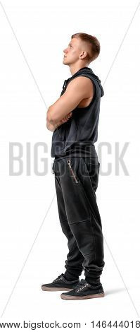 Side view of muscled young man standing with his arms folded looking up, isolated on white background. Bodybuilding and self-improvement. Physical training. Beauty and strength.