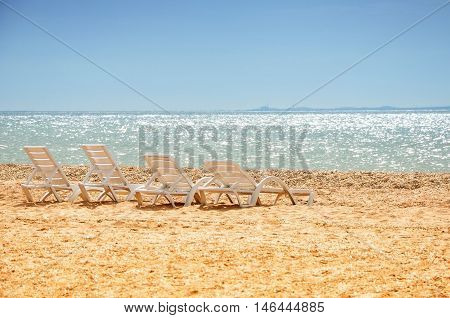 Beach chairs on the sand with the sea in background