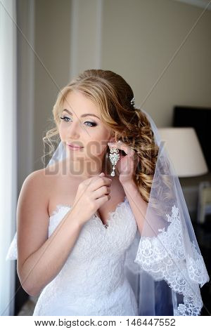 Beautiful bride in white wedding dress puts on earring. Beauty model girl is wearing jewelry. Female portrait in bridal gown for marriage. Woman with curly hair and lace veil. Cute lady indoors