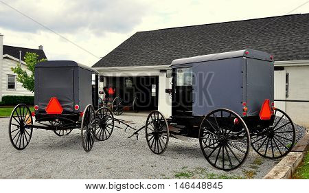 Lancaster County Pennsylvania - June 6. 2015: Amish buggies with enclosed carriages and large wooden wheels parked in front of a farmhouse garage *