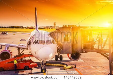 Airplane at sunset in the terminal gate ready for takeoff - Waiting for the flight. Travel around the world