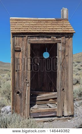 Outhouse: old outhouse against a deep blue sky, in the historic town, Bodie