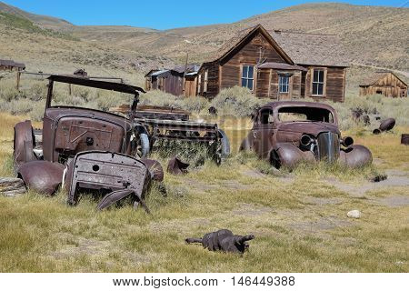 Old Rusty Cars: two vintage cars, rusted, in a field, in the historic ghost town, Bodie