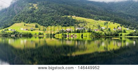 Small village reflection on the banks of a fiord in Norway