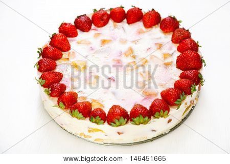Cake with strawberries gelly yogurt and cherries shot from above. Full length. Isolated on white background