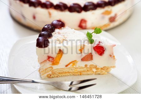 Cake with cherris gelly yogurt and fruits. Isolated on white background. One piece in a white plate. Horizonta; shot