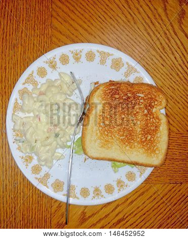 A bacon lettuce and tomato sandwich on toast with a side of salted macaroni salad served on a ceramic plate with a fork on an old wooden table top