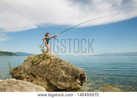 Girl is fishing on the shore of Lake Baikal
