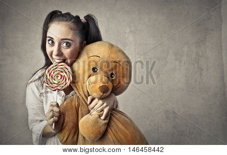 Teenager holding a teddy bear and a lollypop