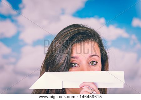 beautiful brunette holding a paperplane covering her nose in front of a cloud themed background ready to throw it with sky background