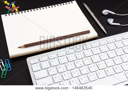 Blank paper on black table with keyboard / for your text or message / top view