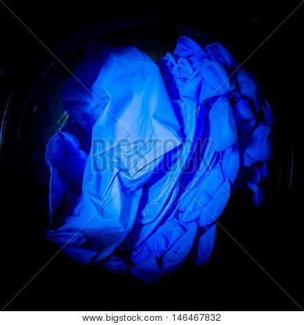 Illuminated blue surgical gloves in dark background