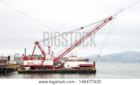 San Francisco CA - August 20 2016: Manson crane on a barge behind the Ferry Building in the San Francisco Bay. Manson works on construction and dredge projects in and around the San Francisco Bay.