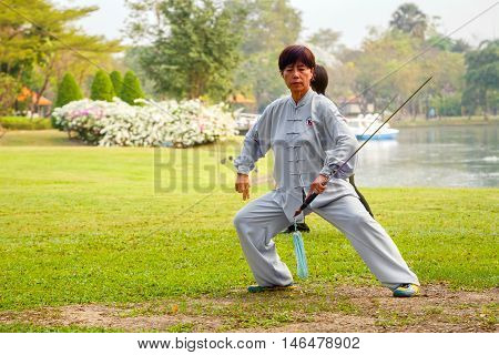 BANGKOK THAILAND - FEBRUARY 20 2016: Unidentified group of people practice Chinese sword with Tai Chi Chuan in a park