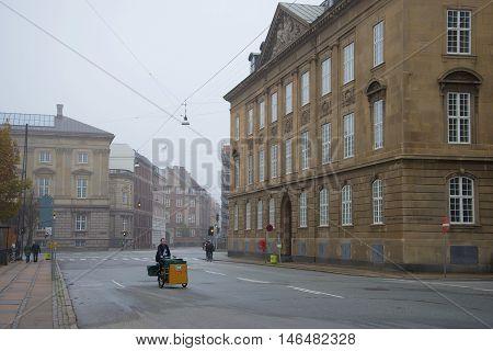 COPENHAGEN, DENMARK - NOVEMBER 01, 2014: The Postman on a city street a foggy november morning. Tourist landmark of the city Copenhagen