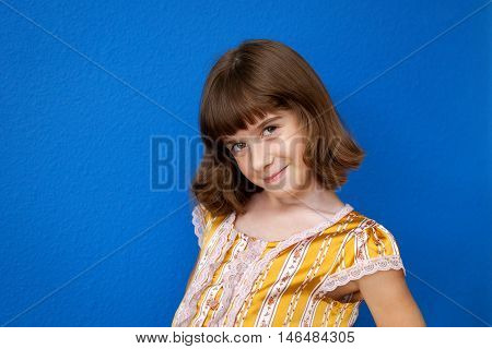 A very confident and sassy looking young girl poses for the camera while showing off her haircut. Copy space.