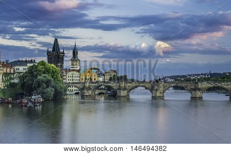 Magical view on the Vltava river Charles bridge and its bridge towers with blue and violet clouds. Dynamic picture from Old Town Prague Czech Republic Europe.