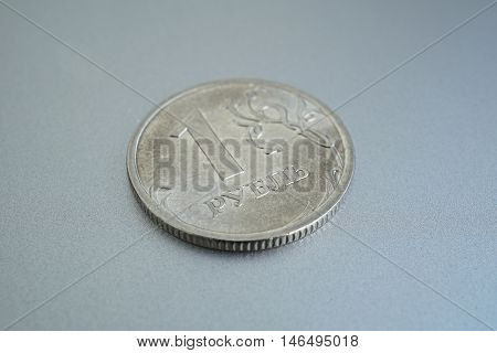 Macro detail of a shiny silver coin of one Ruble (Rouble) as a symbol of Russian currency on the silver background