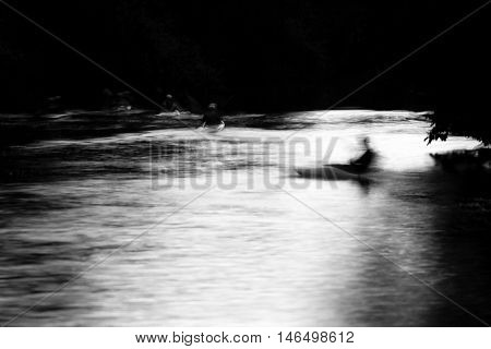 Canoeists on the River Avon by moonlight. Long exposure of people kayaking on river at night in black and white