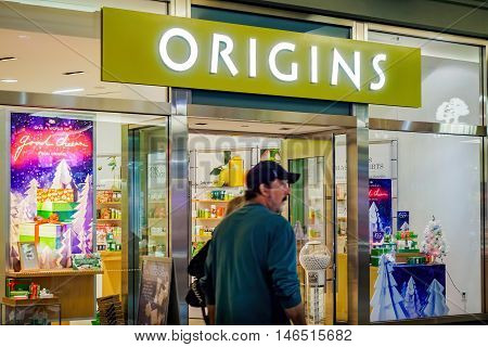 Honolulu, Hawaii, USA - Dec 21, 2015: Night view of the Origins shop front at Ala Moana Center. Origins is a famous cosmetics and beauty supply store. A couple walks pass the shop.