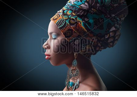young beautiful fashion model with traditional african style with scarf, earrings and makeup on dark blue background.