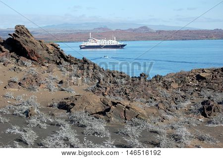 Arid volcanic landscape with cruise ship anchored in Sullivan Bay, Galapagos