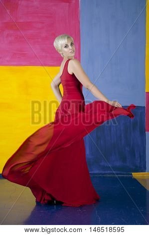 Young beauty woman in fluttering red dress. Multicolor background.