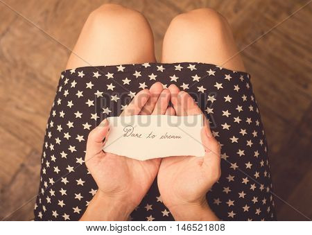Woman with star patterned dress holding a note with dare to dream message on it