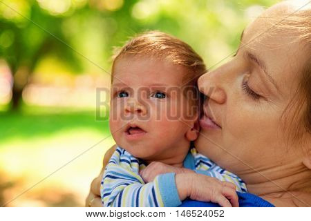 Portrait of mother and baby boy in the park in the summer