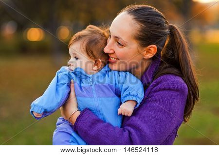 Portrait of mother and baby boy in the park in the autumn. Looking away