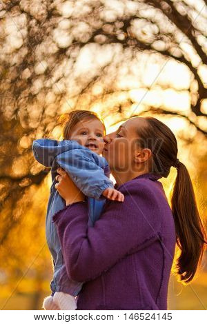 Portrait of mother and baby boy in the park in the autumn. Mother giving a kiss