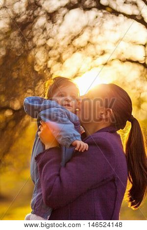 Portrait of mother and baby boy in the park in the autumn. Mother giving a kiss. Sun behind them