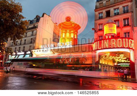 Paris France - September 04 2011 - The famous Moulin Rouge at dawn on a rainy evening. Le Petit Train de Montmartre in front of it is waiting for tourists for a guided trip to the hill.