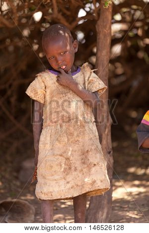 Amboseli Kenya - February 07 2012 - Portrait of masai child in typical clothing in masai village in Amboseli national park