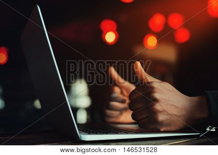 Black man's hands with thumbs up gesture. Gesture All is excellent. Person working with laptop. Beautiful lights as background. Toned style instagram filters.
