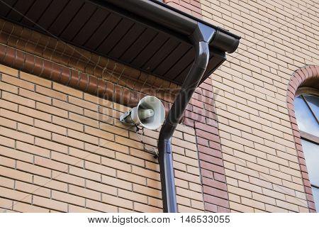 White megaphone hanging on a brick wall