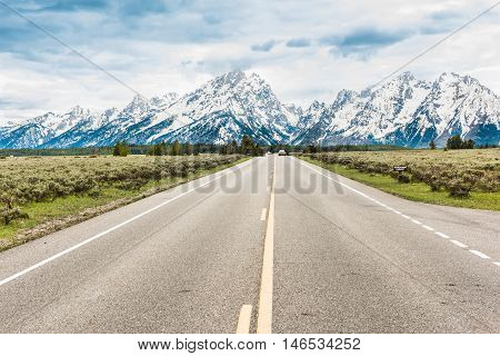 Road with cars leading to Grand Teton mountains in Wyoming national park with cloudy stormy sky