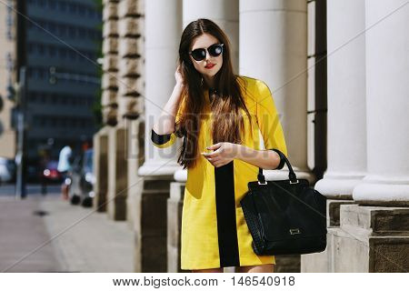 Outdoor portrait of young beautiful lady walking on the street. Model wearing sunglasses and stylish yellow summer dress. Girl looking down. Female fashion concept. City lifestyle. Sunny day. Waist up.