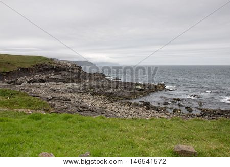 Landscape on the Faroe Islands with ocean white clouds and cliffs